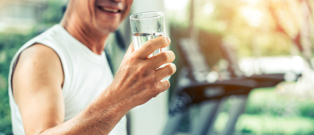 how much water do you need to drink? Senior man drink mineral water in gym fitness center after exercise. Elderly healthy lifestyle.